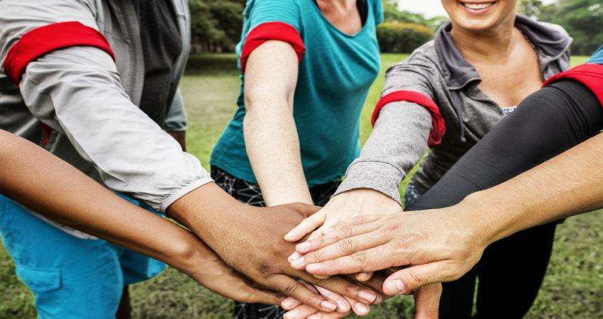 Menschen legen Hände aufeinander