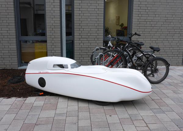 Fahrrad mit Rundumkabine parkt am neuen Rathaus