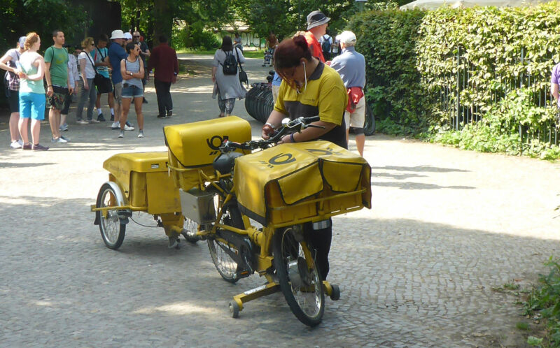 Dienstrad einer Briefträgerin mit Anhänger, Korb und Taschen