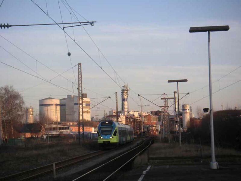Vor der Kulisse der Zuckerfabrik fährt die Westfalenbahn in den Bahnhof Lage ein