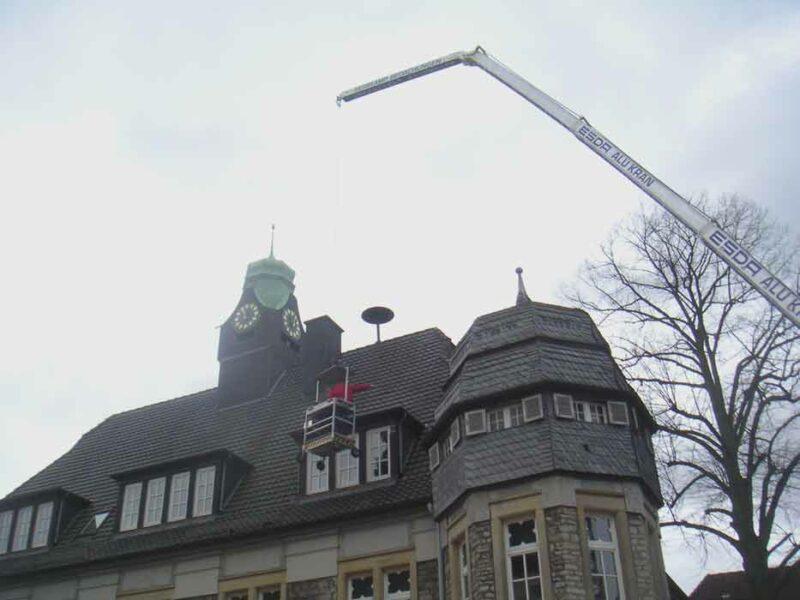 Dachdeckergondel schwebt am historischen Rathaus in Lage