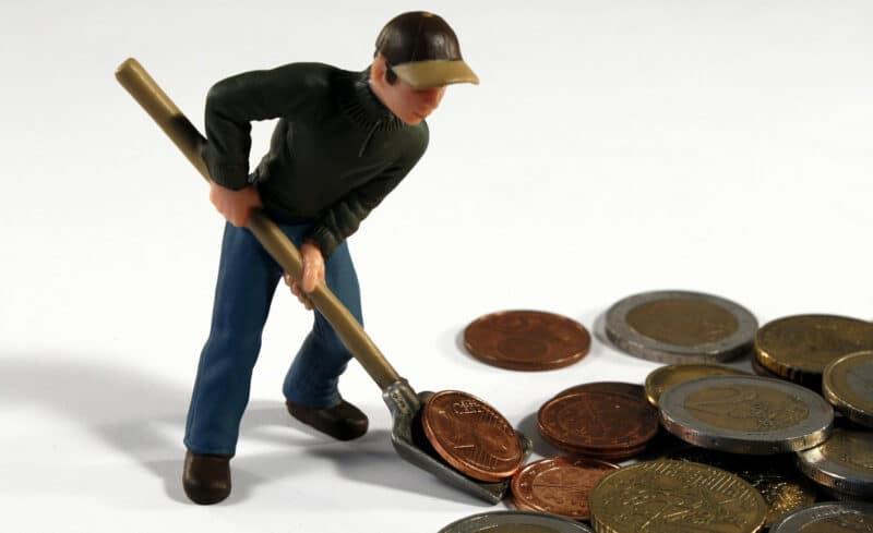 Spielfigur schaufelt Geldmünzen